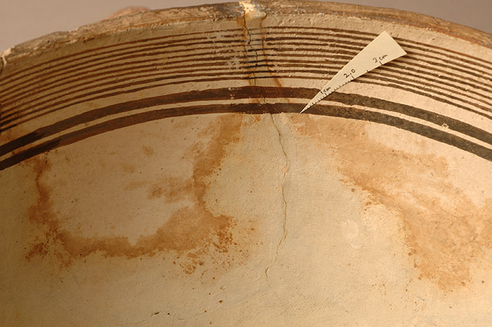 Before the establishment of a modern conservation lab, museum workers and restorers applied substances that interacted badly with original materials. Here, materials used to fill losses in the bowl have leached into the clay body of the pot, causing staining.
